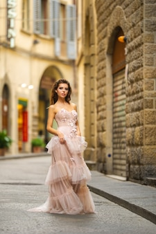 Uma noiva com um vestido de noiva rosa anda em florença, itália.