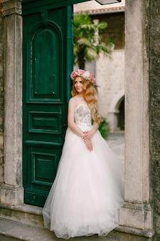 Uma noiva com uma coroa de rosas está parada na porta verde do aconchegante pátio da cidade velha de