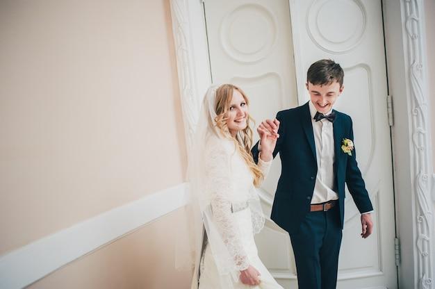 Uma noiva dançando com o noivo e de mãos dadas perto da porta