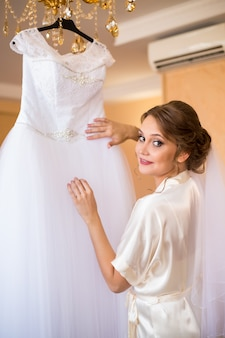 Uma noiva de lingerie vem para o seu vestido de noiva