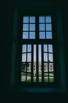 Uma noiva e um noivo beijando fora da grande janela.