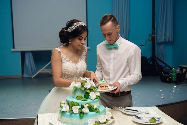 Uma noiva e um noivo está cortando seu bolo de casamento