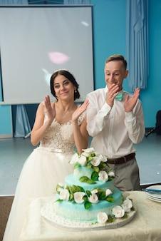 Uma noiva e um noivo estão cortando o bolo de casamento.