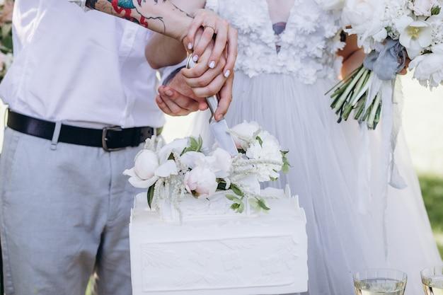 Uma noiva e um noivo estão cortando seu lindo bolo de casamento. nicel light. conceito de casamento