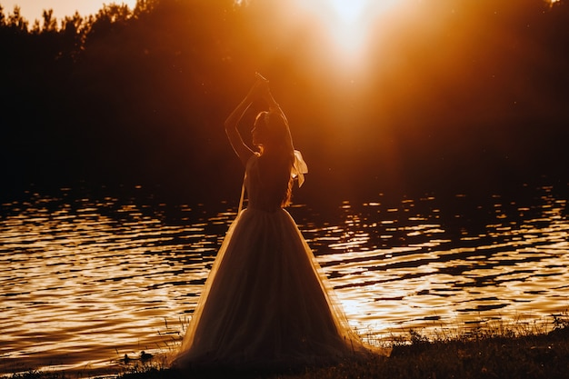 Uma noiva elegante em um vestido branco aprecia a natureza ao pôr do sol. modelo em um vestido de noiva na natureza no parque.