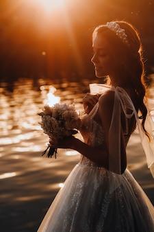 Uma noiva elegante em um vestido branco e luvas está à beira do rio no parque com um buquê, curtindo a natureza ao pôr do sol. uma modelo em um vestido de noiva e luvas em um parque natural.