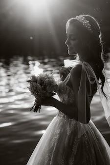 Uma noiva elegante em um vestido branco e luvas está à beira do rio no parque com um buquê