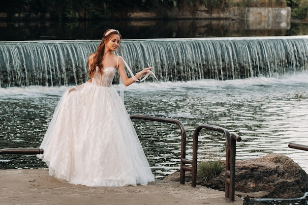 Uma noiva elegante em um vestido branco e luvas está à beira do rio no parque, curtindo a natureza.
