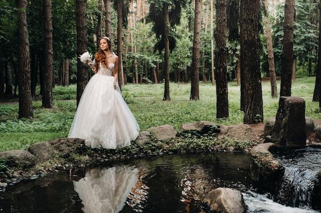 Uma noiva elegante em um vestido branco e luvas segurando um buquê fica perto de um riacho na floresta, curtindo a natureza. uma modelo em um vestido de noiva e luvas em um parque natural.