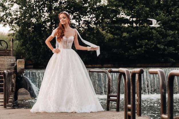 Uma noiva elegante em um vestido branco e luvas segurando um buquê fica perto de um riacho na floresta, curtindo a natureza.