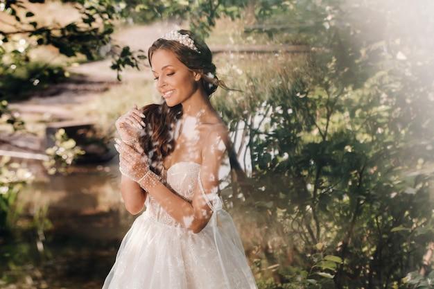 Uma noiva elegante em um vestido branco, luvas com buquê em uma cachoeira no parque, curtindo a natureza. modelo em um vestido de noiva e luvas na floresta.