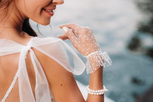 Uma noiva elegante em um vestido branco, luvas e pés descalços está sentada perto de uma cachoeira no parque apreciando a natureza. uma modelo em um vestido de noiva e luvas em um parque natural.