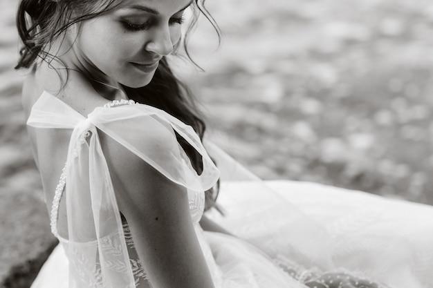 Uma noiva elegante em um vestido branco, luvas e pés descalços está sentada perto de uma cachoeira no parque curtindo a natureza.