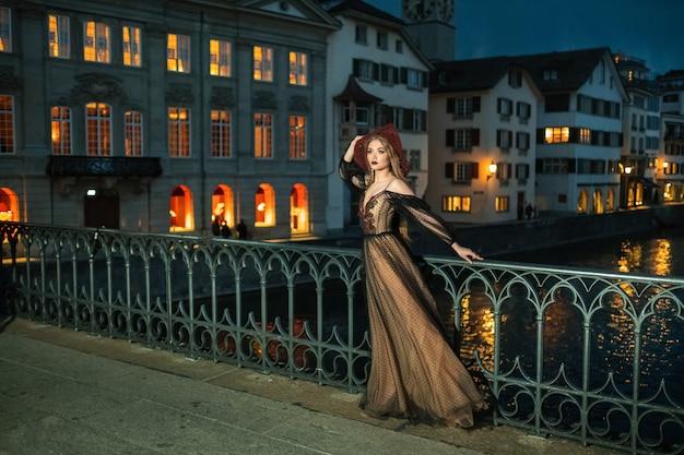 Uma noiva elegante em um vestido de noiva preto e um chapéu vermelho posa à noite na cidade velha de zurique. suíça.