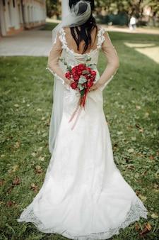 Uma noiva em um lindo vestido com uma cauda segurando um buquê de flores e folhagens.
