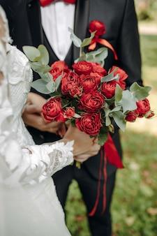 Uma noiva em um lindo vestido com uma cauda segurando um buquê de flores e folhas