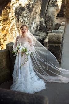 Uma noiva em um vestido branco com um buquê de flores no fundo das montanhas e desfiladeiros na saxônia suíça, alemanha, bastei.