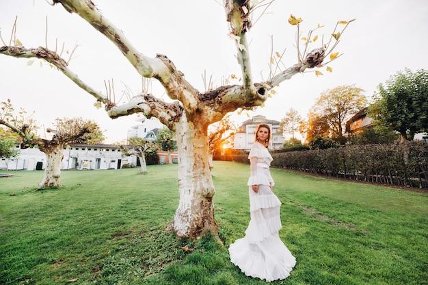 Uma noiva em um vestido de noiva branco com um cinto na cidade velha de velden am werter see.uma modelo em um vestido de noiva austríaco.