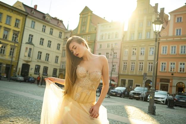 Uma noiva em um vestido de noiva com cabelo comprido na cidade velha de wroclaw. sessão de fotos de casamento no centro de uma antiga cidade em poland.wroclaw, polônia.