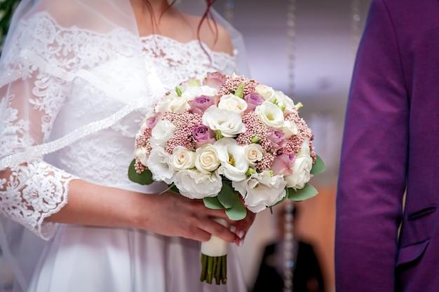 Uma noiva está segurando um buquê de casamento com rosas nas mãos.