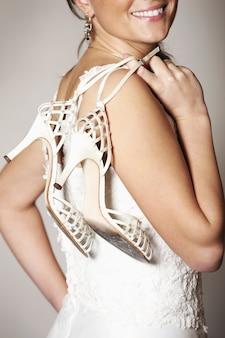 Uma noiva feliz segurando seus sapatos de casamento e sorrindo