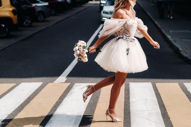 Uma noiva irreconhecível em um vestido de noiva curto branco com um buquê atravessa a rua na cidade em uma passagem para pedestres