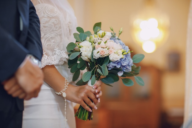 Uma noiva jovem e bonita está de pé com o marido em uma igreja