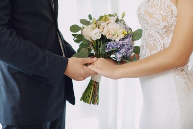 Uma noiva jovem e bonita está de pé com o marido