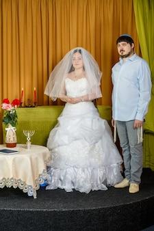 Uma noiva judia com rosto de badeken velado e um noivo em uma sinagoga estão em frente a chupa durante uma cerimônia. foto vertical