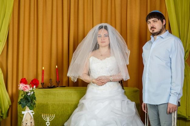 Uma noiva judia com um rosto velado da tradição badeken e um noivo em uma sinagoga estão em frente a chupa durante uma cerimônia