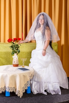 Uma noiva judia em um vestido branco com a cabeça coberta por um véu está em uma sala à mesa