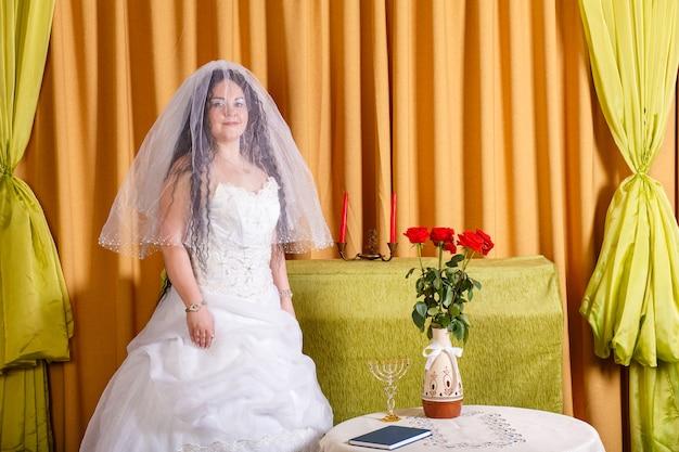 Uma noiva judia em um vestido branco, seu rosto coberto por um véu, está em uma sala em uma mesa com flores, esperando o noivo para a cerimônia da chupa