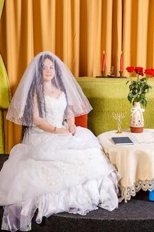 Uma noiva judia em um vestido branco, seu rosto coberto por um véu, senta-se a uma mesa com flores antes da cerimônia chupá. foto vertical