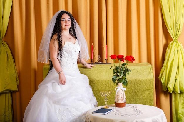 Uma noiva judia em um vestido de noiva branco com um véu está no corredor em uma mesa com flores antes da cerimônia chupa. foto horizontal
