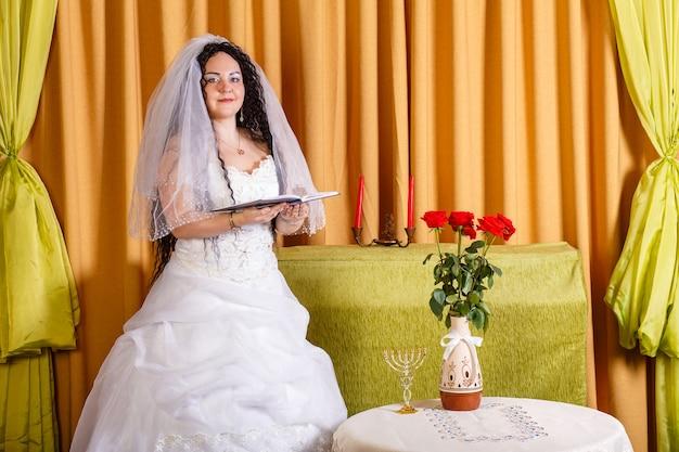 Uma noiva judia em um vestido de noiva branco com um véu está no corredor em uma mesa com flores e reza antes da cerimônia chupá