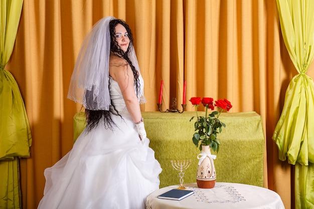 Uma noiva judia em um vestido de noiva branco com um véu está no corredor em uma mesa com flores meio viradas antes da cerimônia chupá. foto horizontal