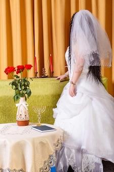 Uma noiva judia em um vestido de noiva branco com um véu está no corredor em uma mesa com flores meio viradas antes da cerimônia chupá