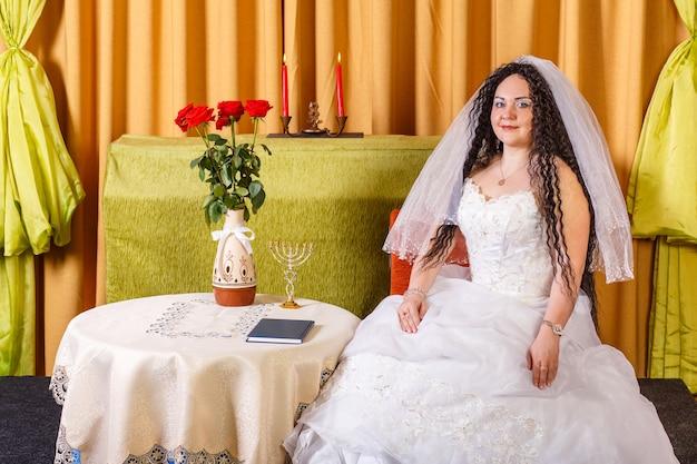 Uma noiva judia em um vestido de noiva branco com um véu está sentada a uma mesa com flores antes da cerimônia chupá. foto horizontal