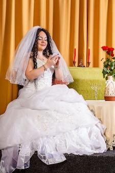 Uma noiva judia em um vestido de noiva branco com um véu está sentada a uma mesa com flores se comunicando em mensageiros instantâneos aceitando os parabéns antes da cerimônia da chupá. foto vertical