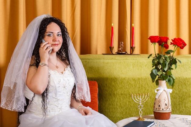Uma noiva judia em um vestido de noiva branco com um véu se senta a uma mesa com flores e fala ao telefone antes da cerimônia chupá