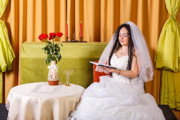 Uma noiva judia em um vestido de noiva branco com um véu se senta a uma mesa com flores e lê as bênçãos de um livro de orações antes da cerimônia chupá