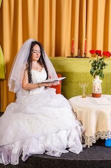 Uma noiva judia em um vestido de noiva branco com um véu sentada a uma mesa com flores
