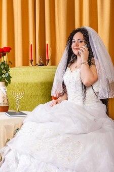 Uma noiva judia em um vestido de noiva branco com véu se senta a uma mesa com flores e fala ao telefone antes da cerimônia chupá. foto vertical