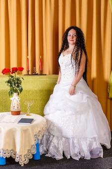 Uma noiva judia em um vestido de noiva branco sem véu está em uma mesa com flores antes da cerimônia chupá