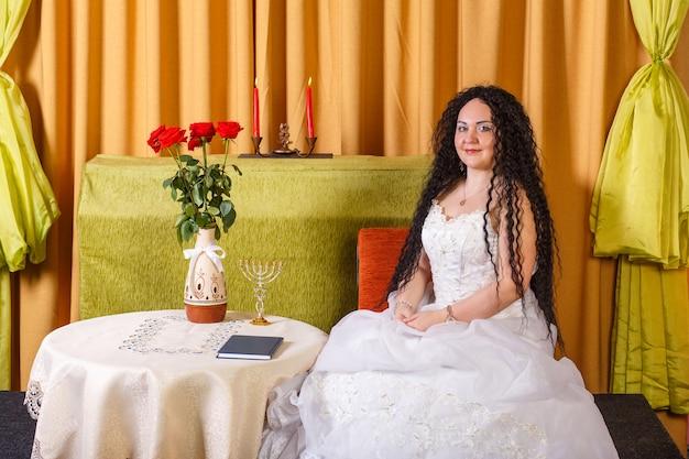 Uma noiva judia em um vestido de noiva branco sem véu está sentada a uma mesa com flores antes da cerimônia chupá. foto horizontal