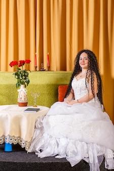 Uma noiva judia em um vestido de noiva branco sem véu está sentada a uma mesa com flores antes da cerimônia chupá. foto vertical