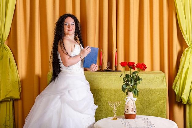 Uma noiva judia em um vestido de noiva branco sem véu segura um livro fechado de tegilim em suas mãos antes da cerimônia chupa. foto horizontal