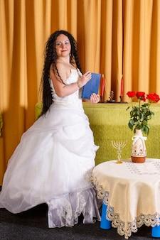 Uma noiva judia em um vestido de noiva branco sem véu segura um livro fechado de tegilim em suas mãos antes da cerimônia chupa