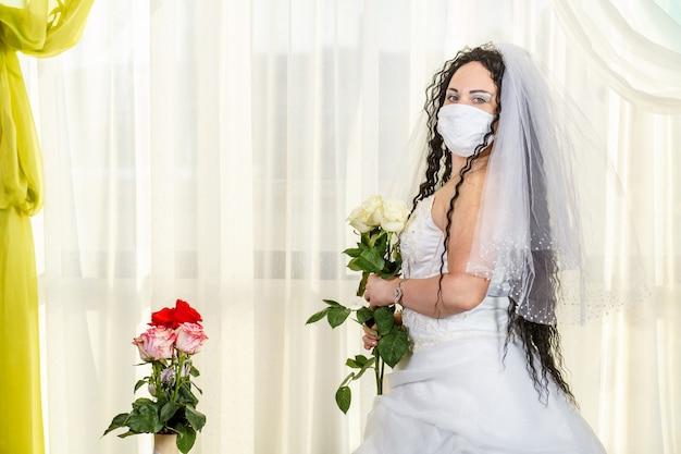 Uma noiva judia em uma sinagoga antes de uma cerimônia huppa durante uma pandemia, usando uma máscara médica e um buquê de flores, espera pelo noivo. foto horizontal