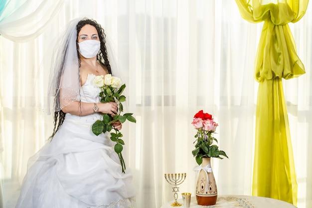 Uma noiva judia em uma sinagoga em uma mesa com flores antes de uma cerimônia chuppa durante uma pandemia, usando uma máscara médica e um buquê de flores, espera o noivo
